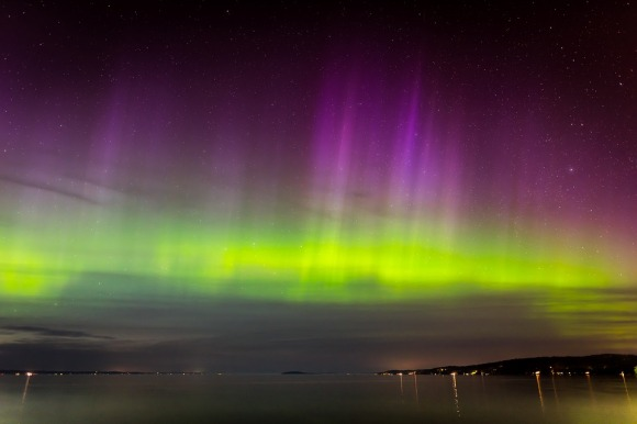 aurora borealis over ocean with the lights of a town in the distance