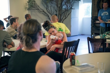 Heather Menzel feeds her daughter, Belle, during a Christian-based drug recovery meeting in Wofford Heights, Calif., in June 2016. Menzel is taking a maintenance dose of methadone to treat her heroin addiction. (Brian Rinker for KHN)