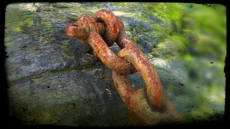 rusty chain bolted to a rock