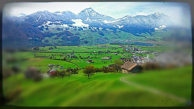 path across field and through village to Alps