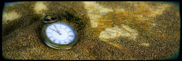 pocket watch on map with sand