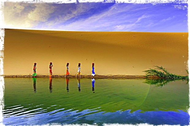 women walking along a lake in front of a sand dune balancing pots on their heads