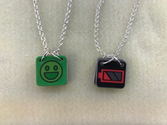 Two communication necklaces strung with silver chain lie on a cream colored beading mat. Each necklace has multiple cards with different faces. The necklace on the left shows a green colored card with a smiley face printed in black. The necklace on the right shows a red-colored low battery icon on a black background. The cards are held to the chains with two silver rings. Flip the cards around the rings to expose different cards.